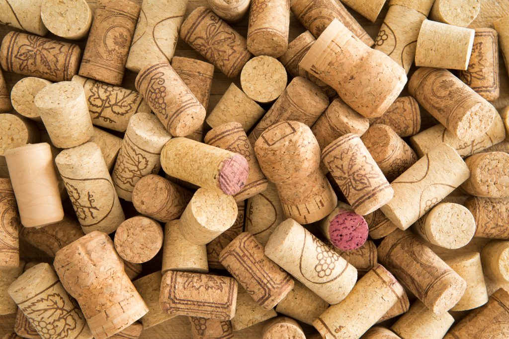 Background texture of a randomly scattered pile of assorted used wine corks with cultivar and winery details on the surface of the corks close up overhead view