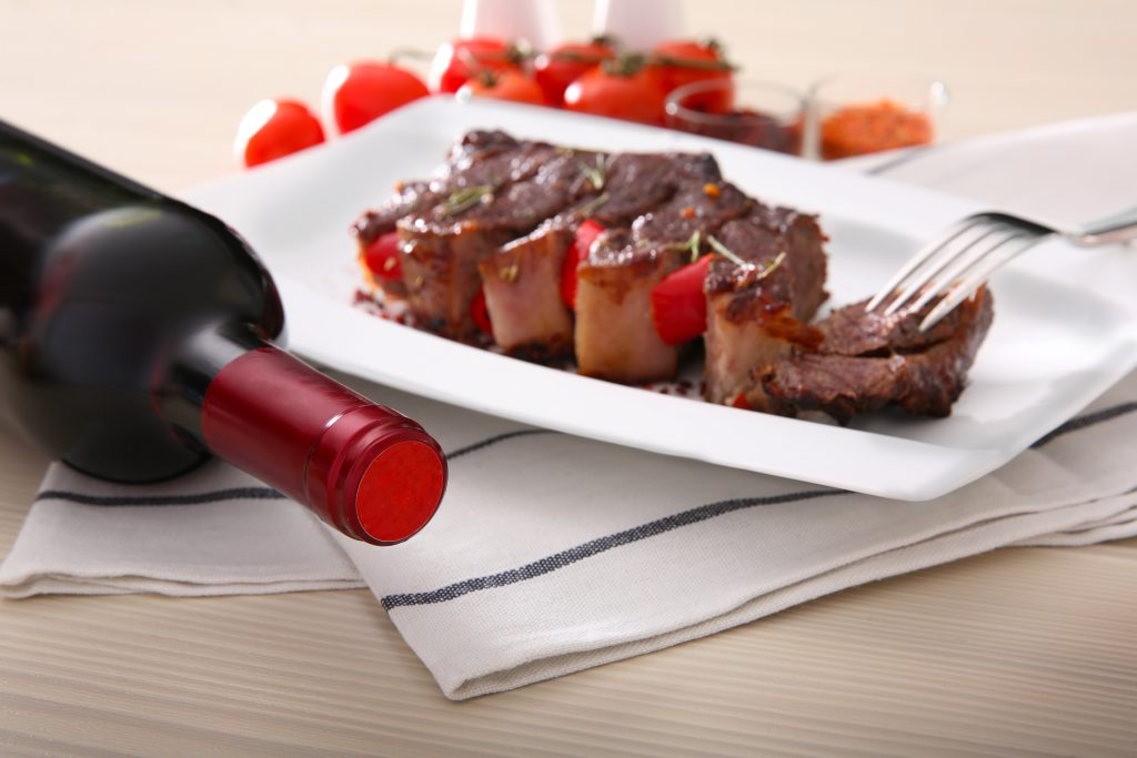 Sliced roasted pork steak with bottle of red wine on white plate
